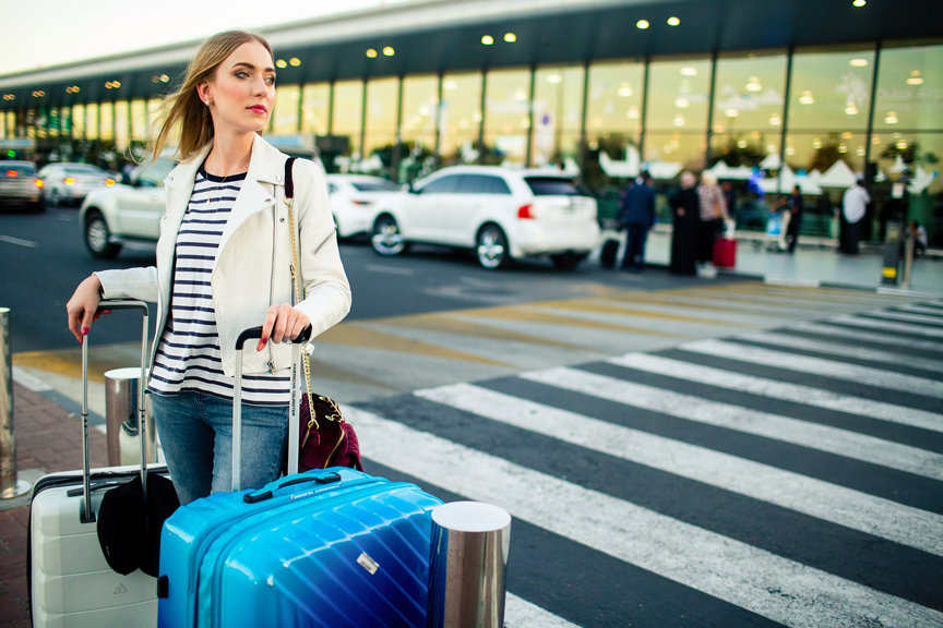 stunning-blonde-lady-with-blue-white-suitcases-stands-before-crossing-street